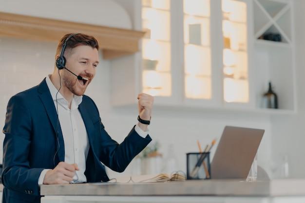 Деловые успехи и достижения. взволнованный счастливый бизнесмен в строгом костюме и гарнитуре празднует успех, поднимает кулак и смотрит в ноутбук, сидя на своем рабочем месте дома