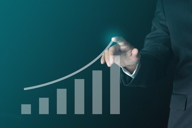 ビジネスの成功の概念。仮想棒グラフで成長線を指すビジネスパーソンは利益を示しています