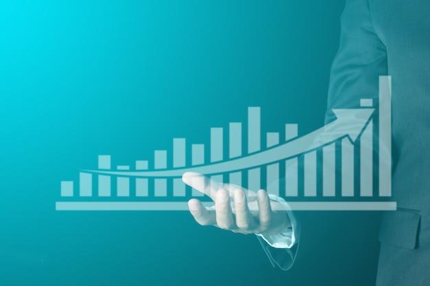 ビジネスの成功の概念。手に仮想棒グラフと矢印を持つビジネスマンは、会社の利益と収益の成長を示しています