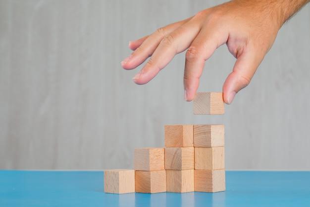 青と灰色のテーブル側ビューのビジネス成功の概念。木製キューブを拾う手。