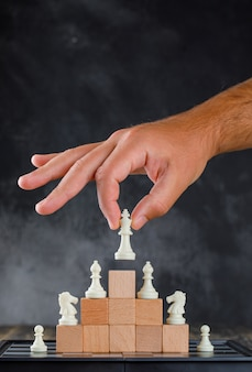 Business success concept with chessboard side view. man placing figure on pyramid of blocks.