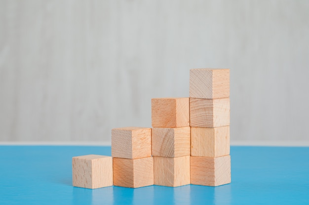 Business success concept with stack of wooden cubes on blue and grey table side view.