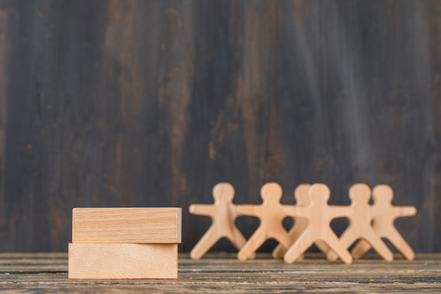 Business success concept with wooden blocks, human figures on wooden table side view.