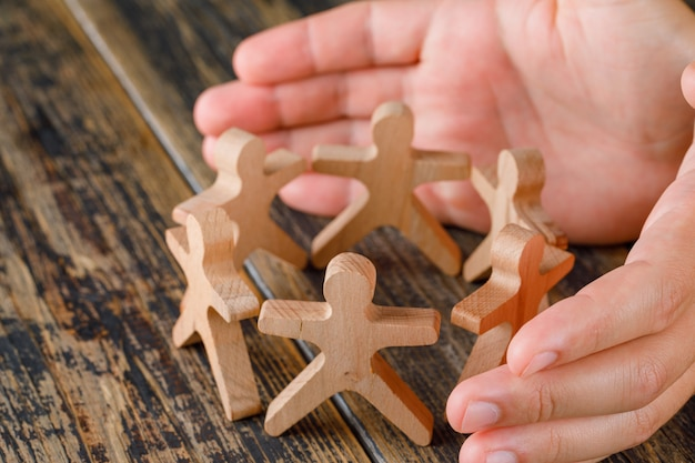 Business success concept on wooden table top view. hands protecting wooden figures of people.