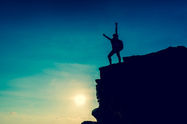 Business success and goal concept. silhouette climber on the cliff.