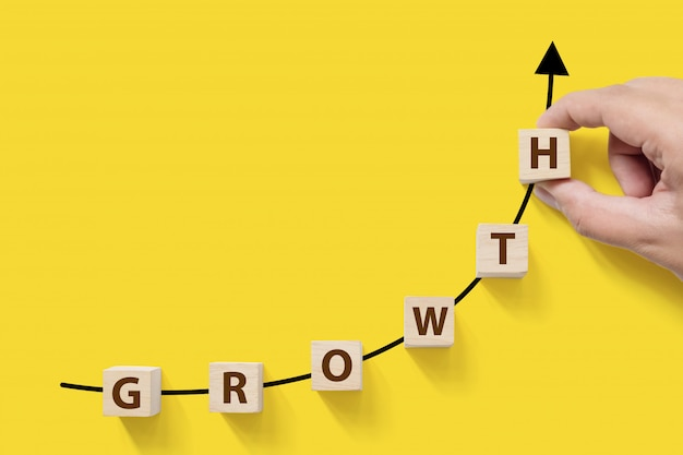 Business success growing growth increase up concept. wooded cube block with word growth