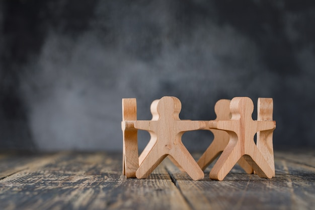 Business success and teamwork concept with wooden figures of people side view.