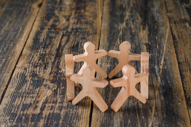 Business success and teamwork concept with wooden figures of people on wooden table top view.