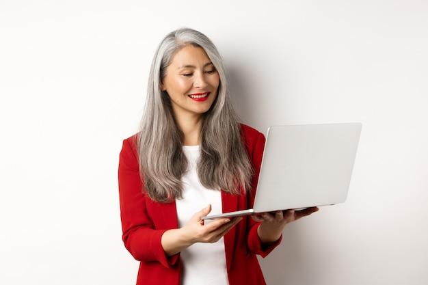 Бизнес. успешная азиатская коммерсантка в красном пиджаке работая на экране компьтер-книжки, усмехаясь и читая, стоя над белой предпосылкой.