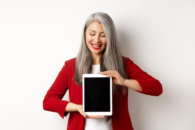Attività commerciale. riuscita imprenditrice asiatica in giacca rossa che mostra lo schermo in bianco della tavoletta digitale, guardando verso il basso con un sorriso soddisfatto, sfondo bianco.