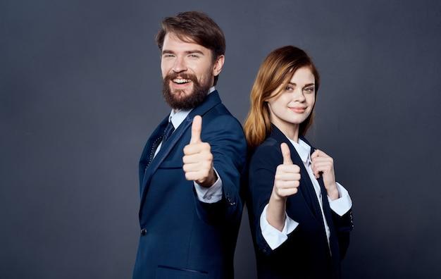 양복을 입은 비즈니스 성공한 사람들은 회색 배경에 서로 등을 대고 서 있습니다.