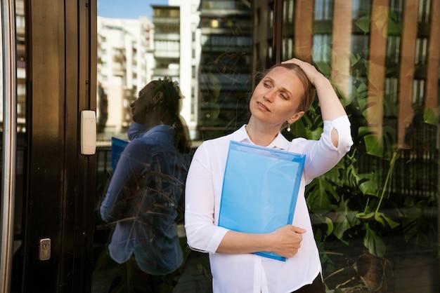 서류에 대 한 파란색 폴더와 흰 셔츠에 비즈니스 성공적인 여자는 사무실 건물에 서