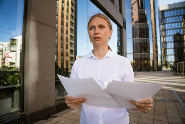 Business successful woman with papers in hand against the background of the office center