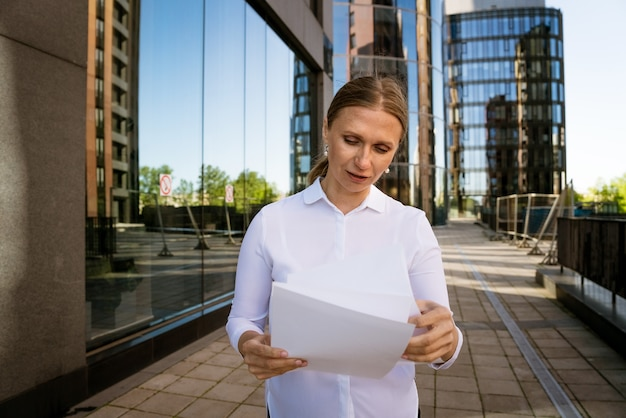 Business successful woman with papers in hand against the office center