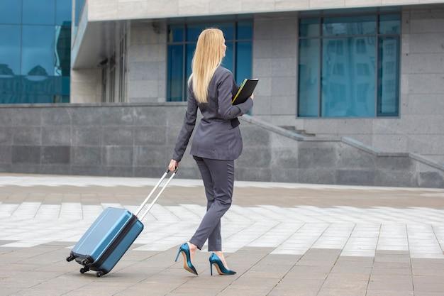 도시 거리에 손에 문서와 여행 가방 비즈니스 성공적인 여자