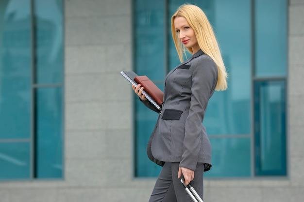 도시 거리에 문서를 들고 여행 가방을 들고 비즈니스 성공한 여성