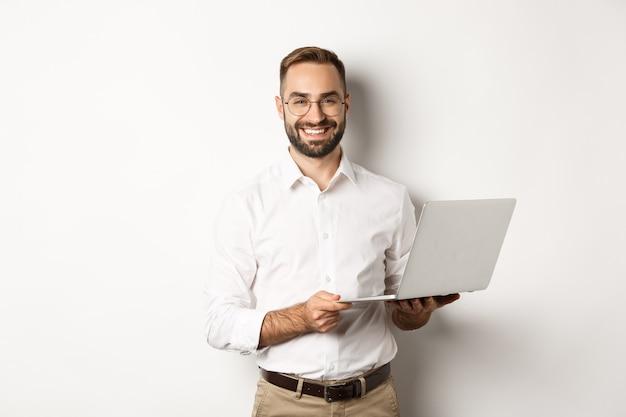 사업. 노트북, 컴퓨터를 사용하고 웃고, 서있는 성공적인 사업가