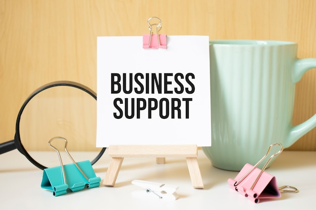 Business support text written on black notebook with magnifying glass and a pen. business and achievement concept.
