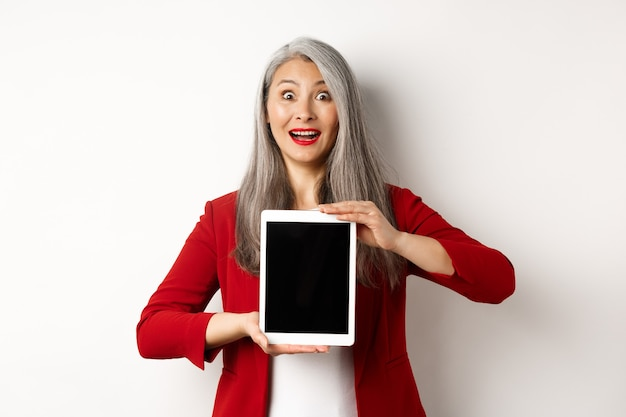 Бизнес. удивленный азиатский женский менеджер показывая пустой экран цифрового планшета, поднимая брови и задыхаясь, очарованный, стоя над белой предпосылкой.