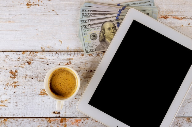 Business tablet us dollars banknotes and coffee cup on wooden table