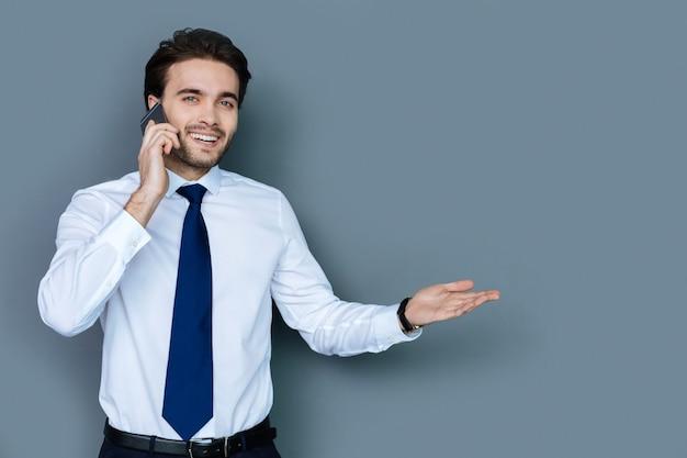 商談。ビジネスの問題を話している間笑顔で電話で会話をしているうれしそうなスマートポジティブビジネスマン