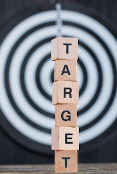 Business target concept with dartboard, wooden cubes on wooden and black background side view.