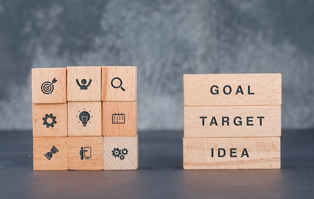 Бизнес-концепция цели с деревянными блоками с иконами на нем вид сбоку.