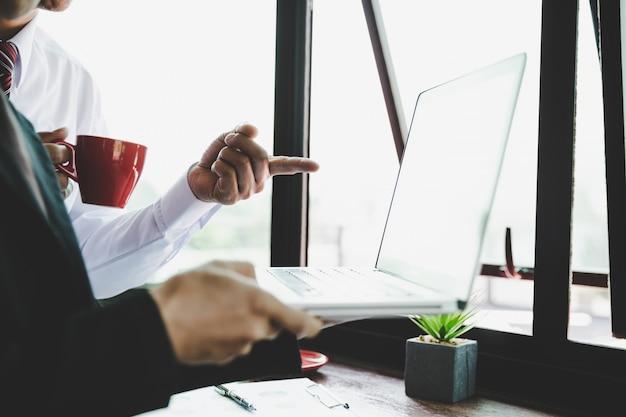 現代のラップトップコンピューターで収入チャートやグラフを分析するビジネスチーム。