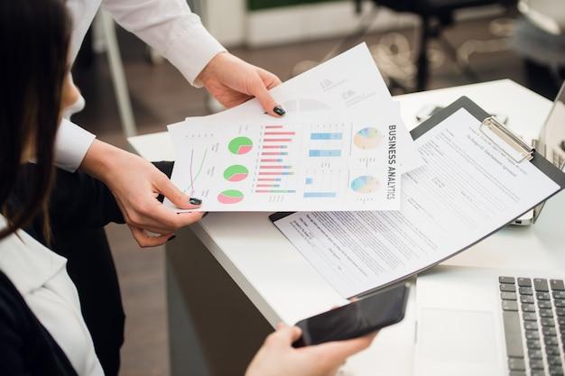 Бизнес-группа анализирует диаграммы и графики доходов с помощью современного портативного компьютера