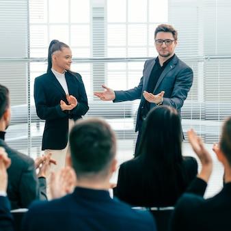 Деловая команда аплодирует на рабочем совещании. концепция успеха