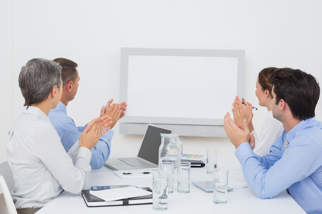 Business team applauding and looking at white screen