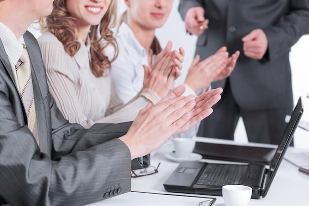 Деловая команда аплодирует, сидя за столом .photo с копией пространства