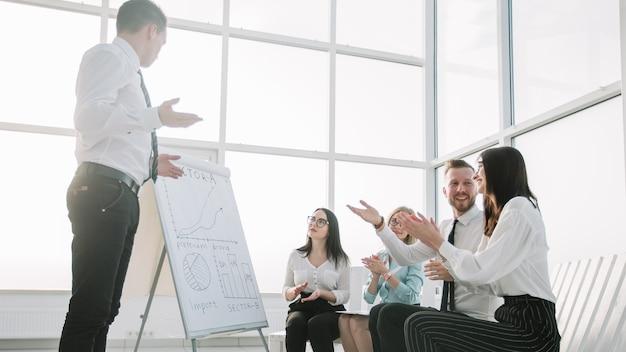 ビジネスチームは、新しいオフィスでのブリーフィングでスピーカーを称賛します。良い仕事の概念