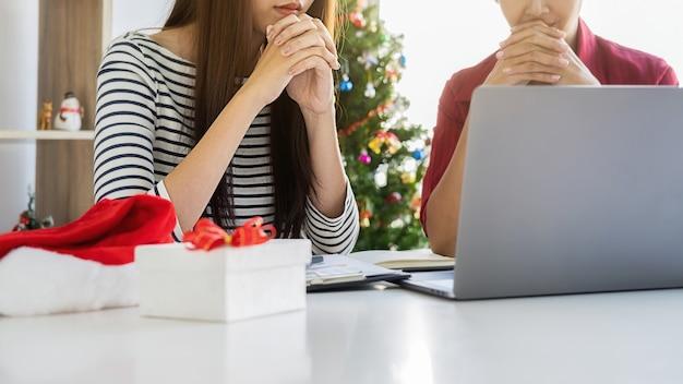ビジネスチームは、最終営業日の財務データとレポートグラフについて話し合っています。若い創造的な人々は、現代のオフィスで休日を祝っています。メリークリスマス、そしてハッピーニューイヤー。