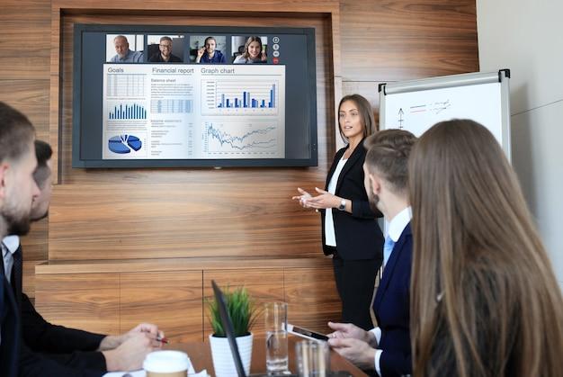 Деловая команда в офисе, бизнесмен, представляющий и обсуждающий успешный финансовый отчет своей компании, на экране плазменного телевизора в конференц-зале, разговаривает со своими коллегами по видеоконференции.