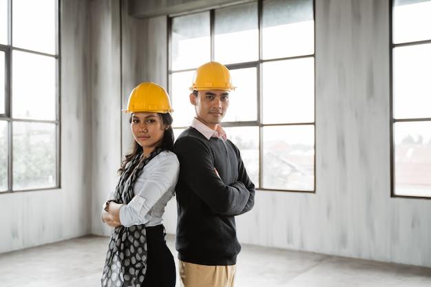 ビジネスチームが背中合わせに腕を組んでヘルメットを着用