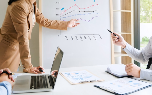 Мозговой штурм бизнес-команды обсуждают результаты продаж на белой доске, а презентация в современном офисном помещении