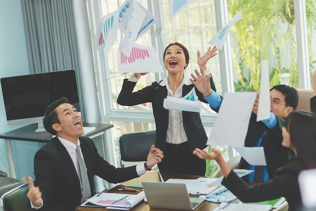 Бизнес-команда празднует, бросая документы на встречу, когда успешно
