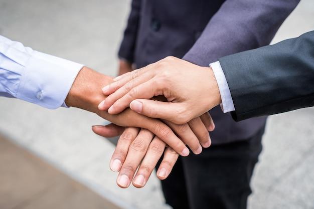 手を積み重ねて団結を示すビジネスチームのコラボレーション
