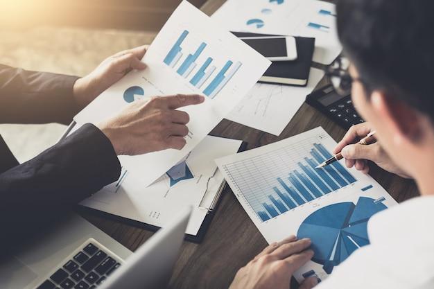 新しい計画の金融グラフデータを議論するビジネスチームの同僚