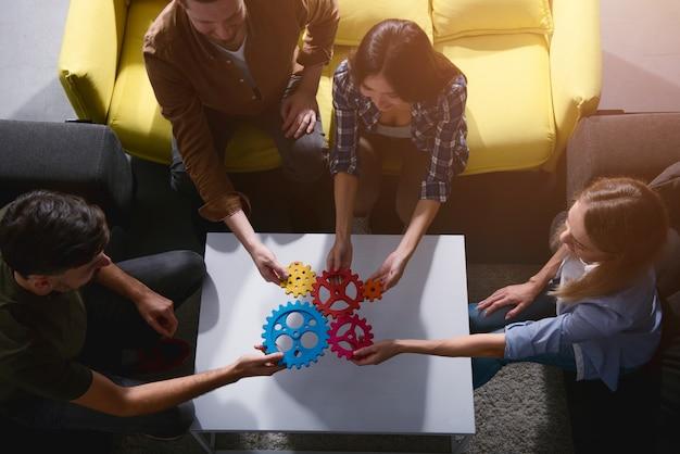 ビジネスチームは、歯車の部分を接続します。チームワーク、パートナーシップ、統合のコンセプト