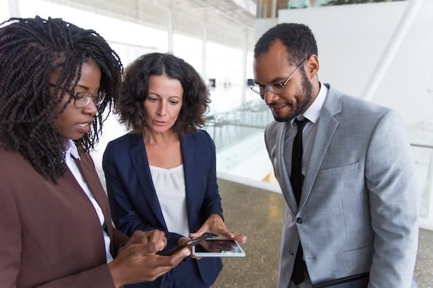 Бизнес-команда вместе консультирует интернет на цифровых устройствах