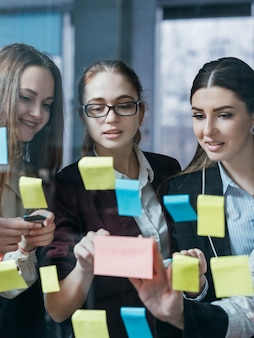 비즈니스 팀 협력. 메모 그룹을 게시하십시오. 사무실 유리 벽에 대한 아이디어를 공유하는 회사 직원.