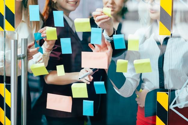비즈니스 팀 협력. 메모 그룹을 게시하십시오. 사무실 유리 벽에 대한 아이디어를 공유하는 회사 직원. 프리미엄 사진