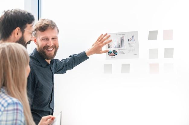Бизнес-команда обсуждает финансовые графики стоя в офисе