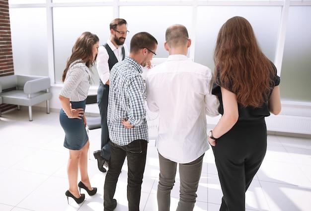 비즈니스 팀은 회의실에 서있는 새로운 아이디어를 논의합니다. 비즈니스 및 교육