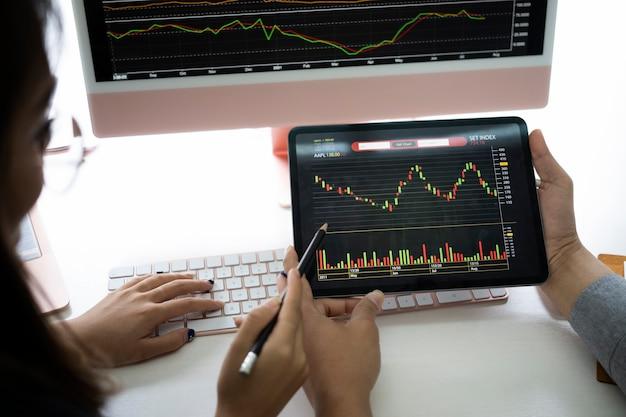 Бизнес-группа обсуждает и анализирует график торговли на фондовом рынке с помощью цифрового планшета.