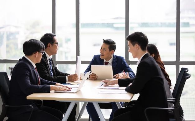 ビジネスチームがオフィスで話し合い、協力する