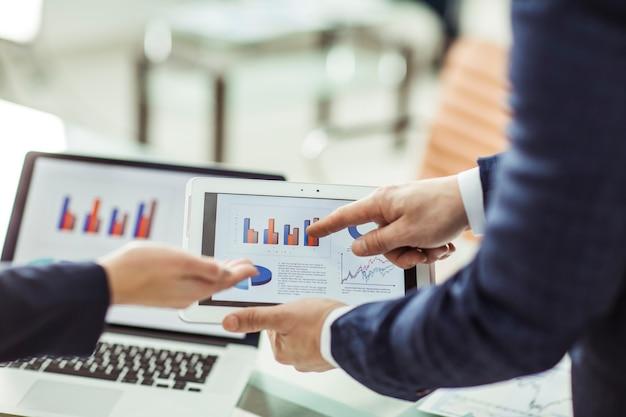 Бизнес-группа обсуждает финансовые диаграммы за своим столом в офисе.