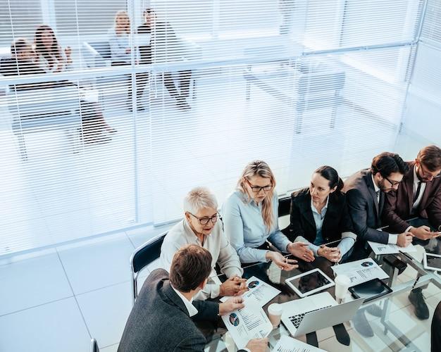 オフィスミーティングで財務データについて話し合うビジネスチーム